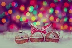 Tarjeta de Navidad del saludo con el oro Jingle Bells en el fondo colorido de Bokeh tono de imagen Fotografía de archivo libre de regalías
