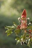Tarjeta de Navidad, duende que se sienta en un acebo Imagenes de archivo