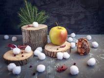 Tarjeta de Navidad El erizo mira una manzana amarillo-roja grande, que se encuentra en el cáñamo del bosque Bolas de nieve, hojas foto de archivo