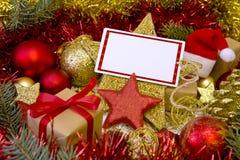 Tarjeta de Navidad en blanco con los regalos, el sombrero de Papá Noel y la decoración Fotografía de archivo libre de regalías