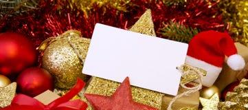 Tarjeta de Navidad en blanco con los regalos, el sombrero de Papá Noel y la decoración Imagen de archivo