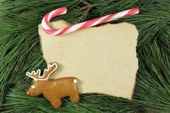 Tarjeta de Navidad en blanco en árbol de abeto con el pan de jengibre del reno Fotos de archivo