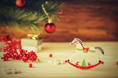 Tarjeta de Navidad en estilo retro Caballo de madera en backgroun borroso Foto de archivo libre de regalías