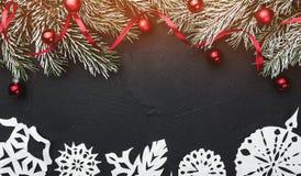 Tarjeta de Navidad En fondo de piedra negro Con el abeto las ramas adornaron con las bolas y la holgura roja Visión superior foto de archivo libre de regalías