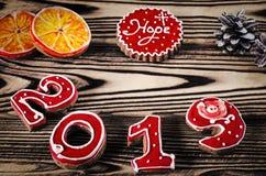 Tarjeta de Navidad en los números rojos 2019 del pan de jengibre de madera del fondo con las rebanadas de naranja imagen de archivo libre de regalías