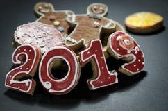 Tarjeta de Navidad en los números rojos 2019 del pan de jengibre oscuro del fondo con las rebanadas de naranja y de hombre de pan foto de archivo libre de regalías