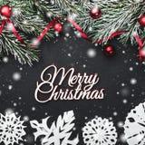 Tarjeta de Navidad En un fondo de piedra negro Con el abeto las ramas adornaron con las bolas y la holgura roja Visión superior imagenes de archivo