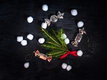 Tarjeta de Navidad Fondo oscuro con la rama del abeto, juguetes de la Navidad bajo la forma de caramelos Una dispersión de bolas  foto de archivo