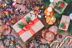 Tarjeta de Navidad Galletas chocolate, regalos, mandarinas, caramelo de la Navidad en fondo de la luz de la falta de definición Imagen de archivo libre de regalías