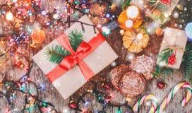 Tarjeta de Navidad Galletas chocolate, regalos, mandarinas, caramelo de la Navidad en fondo de la luz de la falta de definición Foto de archivo