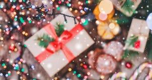 Tarjeta de Navidad Galletas chocolate, regalos, mandarinas, caramelo de la Navidad en fondo de la luz de la falta de definición Fotos de archivo libres de regalías