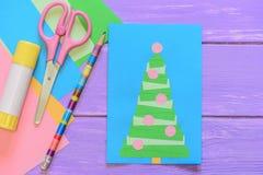 Tarjeta de Navidad hecha en casa fácil, tijeras, palillo del pegamento, lápiz, documento coloreado sobre la tabla de madera púrpu Fotos de archivo libres de regalías