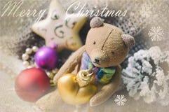 Tarjeta de Navidad hermosa con el oso de peluche, el collar, el cono del pino y los juguetes del árbol de navidad Tarjeta de feli Fotografía de archivo libre de regalías