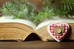 Tarjeta de Navidad: Ornamento en forma de corazón, bayas de la Navidad y un libro viejo Fotos de archivo