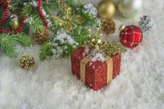 Tarjeta de Navidad Rama del pino, regalo rojo, decoración en un fondo de la nieve Foto de archivo
