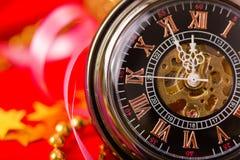 Tarjeta de Navidad reloj del vintage en un fondo rojo con el de oro Fotos de archivo libres de regalías