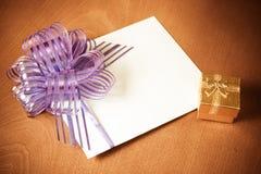 Tarjeta de nota con la caja de regalo púrpura del arco y del oro Estilo de la vendimia Imagen de archivo