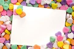 Tarjeta de nota en blanco rodeada, enmarcado por los corazones del caramelo Fotos de archivo