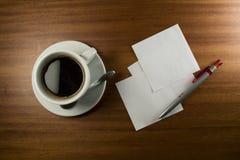 Tarjeta de nota, pluma y taza de café Imágenes de archivo libres de regalías