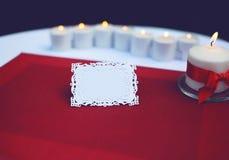Tarjeta de papel para un texto en la tabla adornada con las velas ardientes Fotografía de archivo