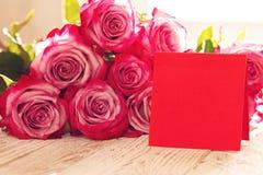 Tarjeta de papel roja en blanco para las tarjetas del día de San Valentín o el día de la madre o de la mujer Fondo con las rosas  Foto de archivo