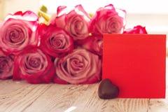 Tarjeta de papel roja en blanco para las tarjetas del día de San Valentín o el día de la madre o de la mujer Fondo con las rosas  Imagenes de archivo
