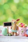 Tarjeta de pascua con el conejo de la arcilla y decoraciones en backgrou de la primavera Foto de archivo libre de regalías