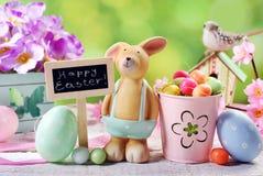 Tarjeta de pascua con el conejo de la arcilla y decoraciones en backgroun de la primavera Fotografía de archivo