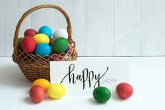 Tarjeta de pascua con los huevos de Pascua coloridos en un ` feliz de Pascua de la cesta y del ` caligráfico de la inscripción Imagen de archivo