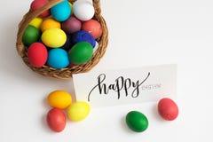 Tarjeta de pascua con los huevos de Pascua coloridos en una cesta y una inscripción caligráfica Pascua feliz Fotografía de archivo