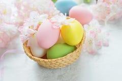 Tarjeta de pascua con los huevos de Pascua y las flores rosadas foto de archivo