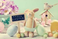Tarjeta de pascua del estilo del vintage con el conejo de la arcilla y decoraciones en m Foto de archivo libre de regalías