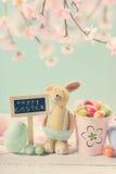 Tarjeta de pascua del estilo del vintage con el conejo de la arcilla y decoraciones en m Fotos de archivo libres de regalías