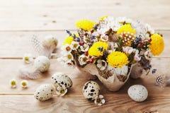 Tarjeta de pascua feliz con las flores, la pluma y los huevos de codornices coloridos en fondo de madera rústico Composición herm foto de archivo