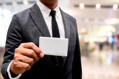 Tarjeta de presentación de la demostración del hombre de negocios con el fondo de la falta de definición Imagen de archivo libre de regalías