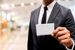 Tarjeta de presentación de la demostración del hombre de negocios con el fondo de la falta de definición Fotografía de archivo libre de regalías
