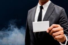 Tarjeta de presentación de la demostración del hombre de negocios con humo Imagenes de archivo