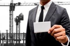 Tarjeta de presentación de la demostración del hombre de negocios con la grúa de construcción Fotografía de archivo