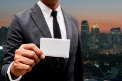 Tarjeta de presentación de la demostración del hombre de negocios con la luz de la ciudad en fondo Imagen de archivo