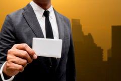 Tarjeta de presentación de la demostración del hombre de negocios con la luz de la ciudad en fondo Imagenes de archivo