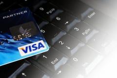 Tarjeta de Redit en el teclado de ordenador con VISA del logotipo de la marca Foto de archivo libre de regalías