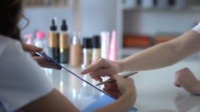 Tarjeta de relleno de los clientes del cosmetólogo antes de designar los procedimientos, cuidado para los clientes almacen de metraje de vídeo