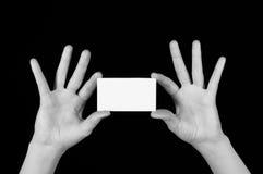 Tarjeta de visita blanca en manos femeninas Imágenes de archivo libres de regalías