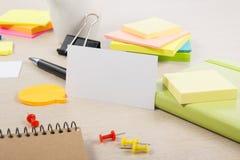 Tarjeta de visita en blanco blanca Escritorio de la tabla de la oficina con el sistema de fuentes coloridas, taza, pluma, lápices Fotos de archivo libres de regalías