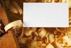Tarjeta de visita en blanco en la tabla de madera para las herramientas del carpintero con la opinión superior del serrín Imagen de archivo libre de regalías