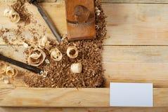 Tarjeta de visita en la tabla de madera para las herramientas del carpintero con serrín Fotos de archivo