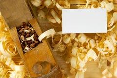 Tarjeta de visita en la tabla de madera para las herramientas del carpintero con serrín Imagenes de archivo