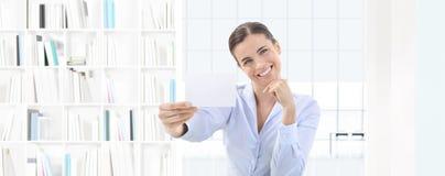 Tarjeta de visita sonriente de demostración de la mujer en su mano en offi interior imágenes de archivo libres de regalías