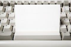 Tarjeta de visita y teclado de ordenador en blanco imagen de archivo