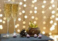 Tarjeta del Año Nuevo con champán y chocolates en el fondo de las guirnaldas del día de fiesta Fotografía de archivo
